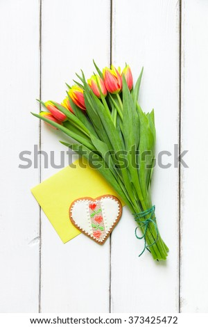 Heart shaped cookie and tulip flowers for Valentines or Mathers day. Top view with copy space. - stock photo