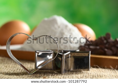 Heart-shaped cookie cutter leaning against a star-shaped cutter with baking ingredients like wheat flour, chocolate chips, eggs in the back (Selective Focus, Focus on the heart-shaped cookie cutter) - stock photo