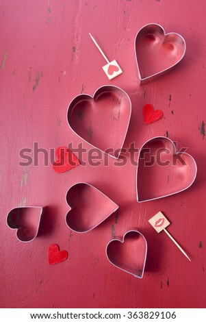 Heart Shaped Cookie Cutters on a rustic red wood table background.