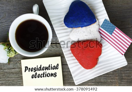 Heart shaped cookies color red, blue, white. Cup of coffee (tea), USA flag, decoration on old wooden table. Patriotic Breakfast Concept - presidential elections - stock photo