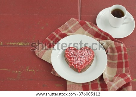 Heart shaped cookies decorated with red sugar glaze and sprinkles served with a cup of espresso.