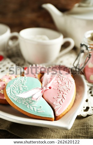 Heart shaped cookies for valentines day and teapot on  wooden background - stock photo