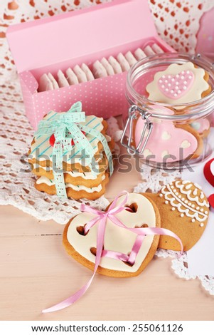 Heart shaped cookies for valentines day on plate, tea bags and card on color wooden background - stock photo