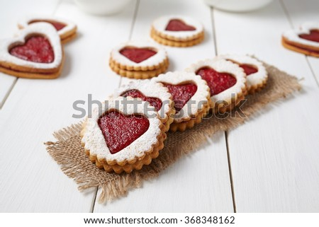 Heart shaped cookies with jam, delicious homemade holiday surprise sweet on white wooden background for Valentines day celebration. - stock photo