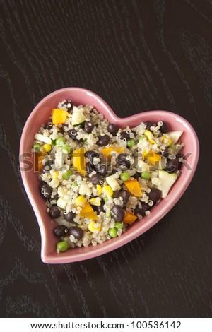 Heart-shaped dish of quinoa salad on a dark wood table - stock photo