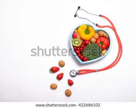 Heart shaped dish with vegetables and stethoscope isolated on white background - stock photo