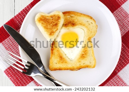 Heart shaped egg in toast for Valentines Day with checked cloth      - stock photo