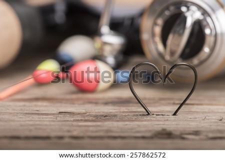 Heart shaped fishing hooks and fishing tools - stock photo