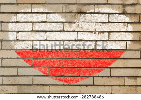 heart shaped flag in colors of Poland on brick wall - stock photo