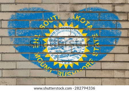 heart shaped flag in colors of south dakota on brick wall - stock photo