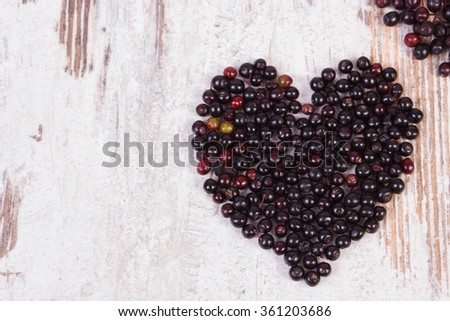 Heart shaped fresh elderberry on old rustic wooden background, symbol of love, copy space for text, healthy nutrition and alternative medicine - stock photo