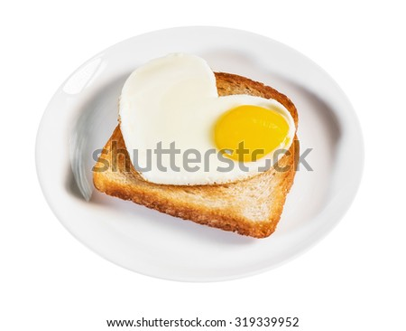 heart-shaped fried eggs and fried toast isolated on a white background. focus on egg yolk - stock photo