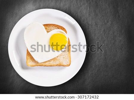 heart-shaped fried eggs and fried toast on a black background. - stock photo