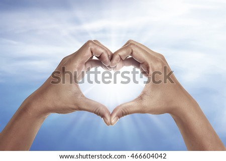heart shaped hand with blue sky background. heart shaped hand is a symbol of love, freedom, romance,
