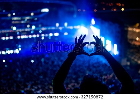 Heart shaped hands at concert, loving the artist and the festival. Music concert with lights and silhouette of a man partying - stock photo