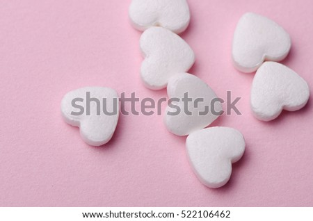 Heart shaped healthcare pills on a neat pink background