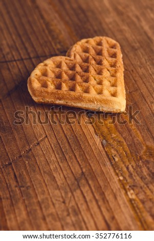 Heart shaped homemade waffle on wooden desk, retro toned, selective focus