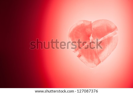 Heart shaped ice cube is cracked - stock photo