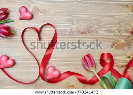 heart-shaped macaroons with flowers and ribbon on a wooden table. Creative decoration for Valentine's Day