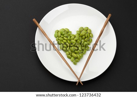 Heart shaped made of fresh green soybeans on a white plate with chopsticks - stock photo