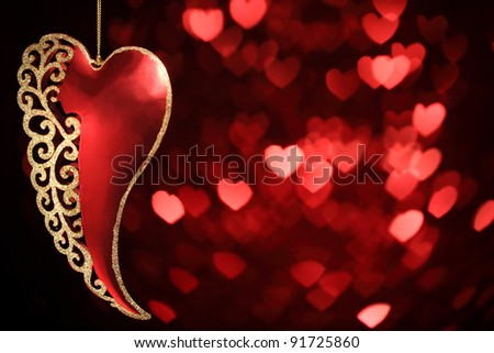 Heart shaped ornament hanging on defocused bokeh background - stock photo