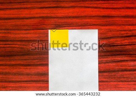Heart shaped paper clip attached to a sheet of paper with a yellow sticky note - stock photo