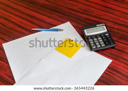 Heart shaped paper clip attached to a sheet of paper with a yellow sticky note. Calculator and pen laying aside - stock photo