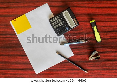 Heart shaped paper clip attached to a sheet of paper with a yellow sticky note. Calculator, pencil and pen laying aside - stock photo