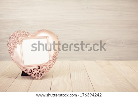 Heart shaped photo frame on wooden table - stock photo