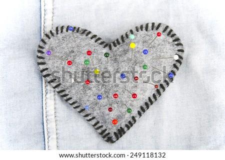 Heart shaped pincushion on blue background - stock photo