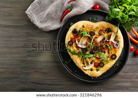 Heart shaped pizza on metal tray on wooden background