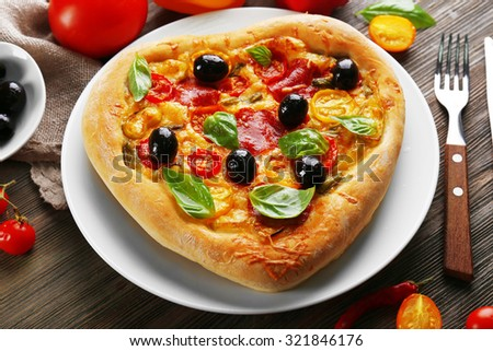 Heart shaped pizza served on plate on wooden background