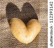 heart shaped potato on hessian - stock photo