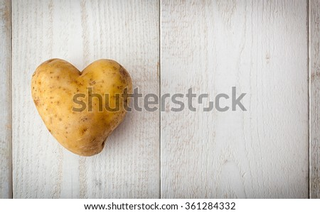 Heart shaped potato on white wooden table.