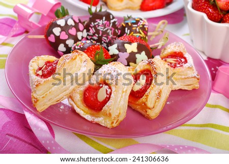 heart shaped puff pastry cookies with strawberries on pink plate for valentines - stock photo