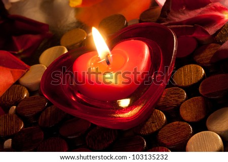 Heart shaped red candle covered with flower petals - stock photo
