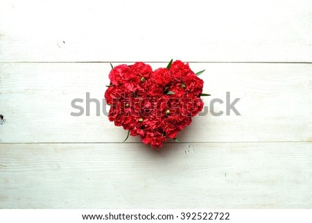 Heart shaped red carnations flower arrangement on the white wooden background - stock photo