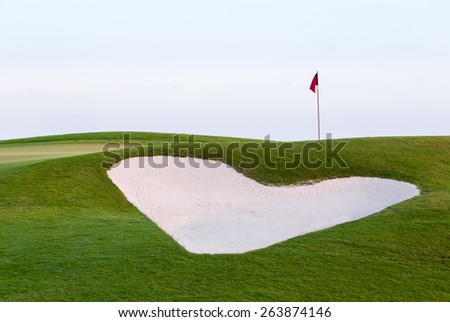 Heart shaped sand bunker in front of red flag of golf hole on beautiful course at sunset illustrating love for game of golf - stock photo