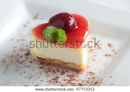 Heart-shaped slice of cheesecake with cherry jam