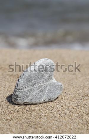 heart shaped stone on sand - stock photo