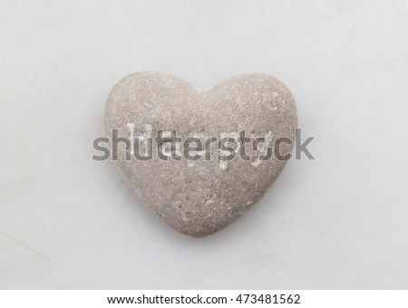 heart shaped stone with text message happy