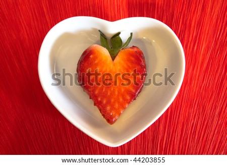 Heart shaped strawberry served in a tiny white dish - stock photo