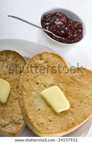 Heart shaped toast with butter on a plate, a pot of Strawberry jam with spoon at the side and a white table cloth background. - stock photo