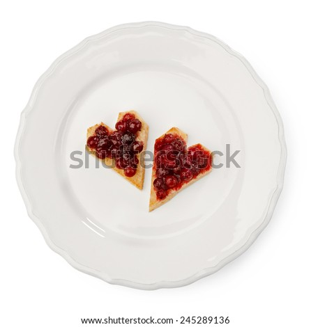 heart-shaped toast with cranberry jam on white plate against white background - stock photo