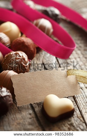 Heart-shaped Truffle with a message card with a pink ribbon on wooden background - stock photo