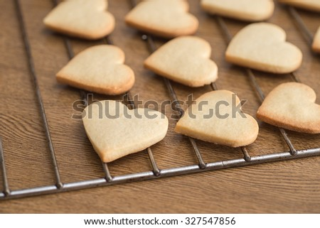Heart shaped valentine's butter cookies cooling on the rack - stock photo
