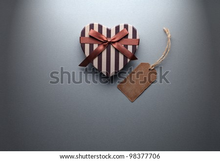 Heart shaped Valentines Day gift box with blank gift tag on gray paper background. - stock photo