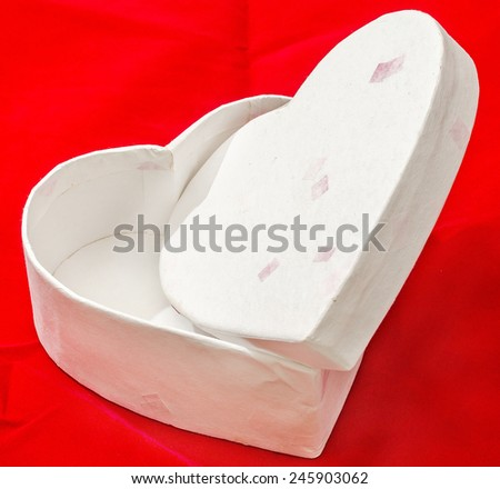 Heart shaped Valentines day white boxes, red background, close up, isolated.