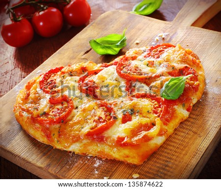 Heart shaped vegetarian pizza topped with cheese and tomato on an old wooden board signifying love of pizza, or romantic love for Valentines day or an anniversary - stock photo
