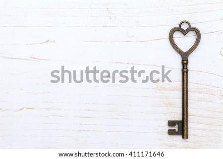 heart shaped vintage key on white wood background - stock photo